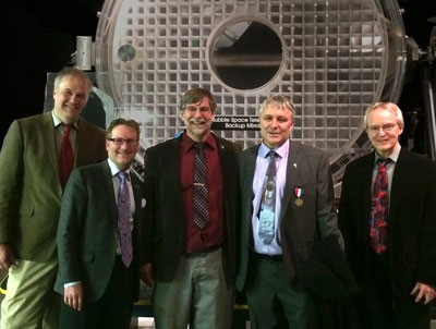 From left to right WFPC2 team members, Chris Burrows, Jim Fansen, Jeff Hester, Karl Stapelfeldt, and John Clarke standing in front of the Hubble back-up mirror at Hubble's 25th Anniversary celebration at the National Air & Space Museum.