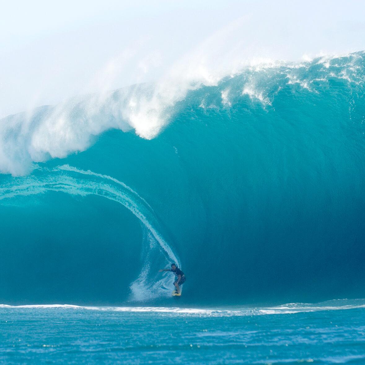 Surfer riding huge wave.